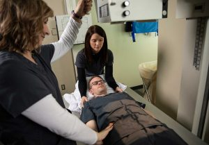 Rad tech students help with patient positioning;