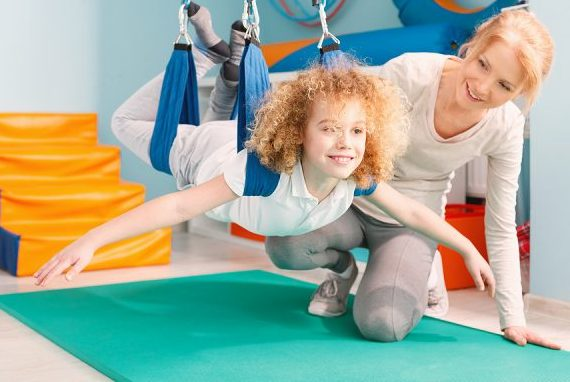 Boy and his therapist exercising during sensory integration therapy;