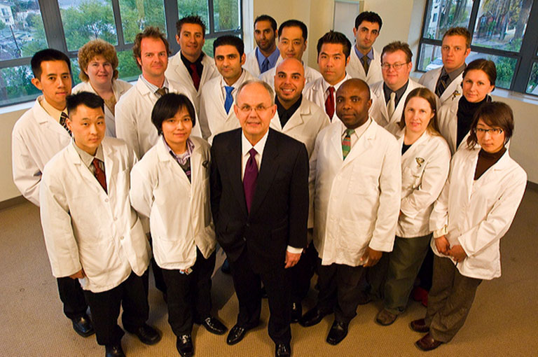 Dr. Cleveland with a group of chiropractic students in their lab coats