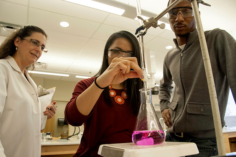Female and male student partaking in chemistry lab while professor helps guide them