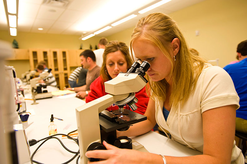 Female student looking through microscope while working with classmate